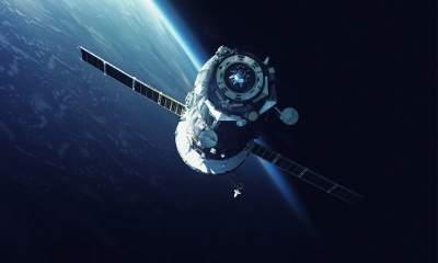 Satellite heading towards a space shuttle in orbit around earth